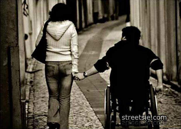 quadriplegic wheelchair love couple holding hands