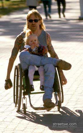 Spinal cord injury wheelchair father carrying child